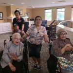 Residents Carmen, Lourdes and Howard are being escorted to the patio for lunch.